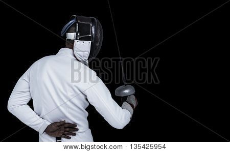 Man wearing fencing suit practicing with sword against black background