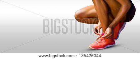 Close up of sportswoman is lacing shoes against grey vignette
