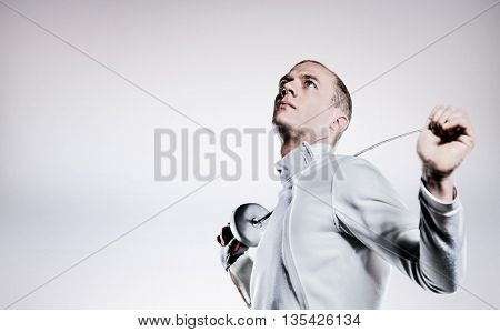 Swordsman holding fencing sword against grey background