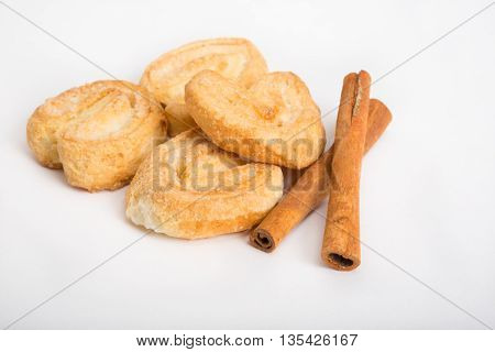 Baked rolls with cinnamon sticks ona white table