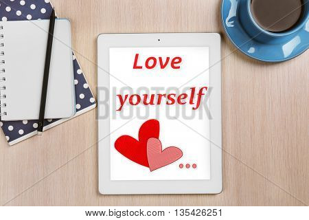Tablet with text Love yourself and cup of coffee on wooden table