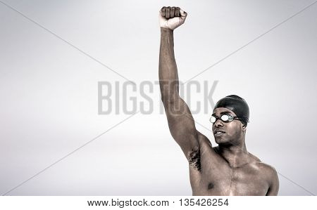 Swimmer posing after victory against grey background