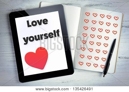 Modern tablet with text Love yourself on screen and notebook on white wooden background