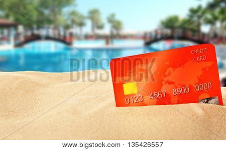 Red bank card in sand on blurred resort background