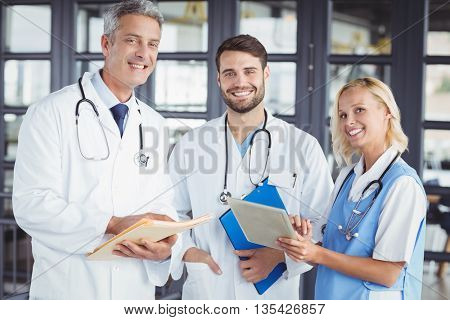 Portrait of smiling senior doctor with coworkers at hospital
