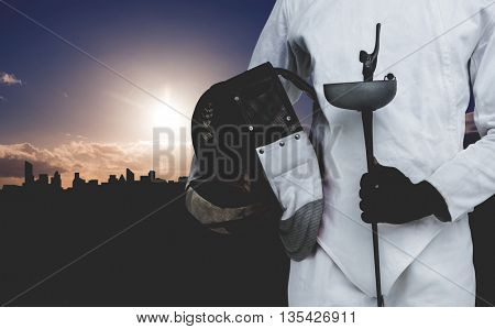 Mid-section of man standing with fencing mask and sword against picture of a city by sunrise