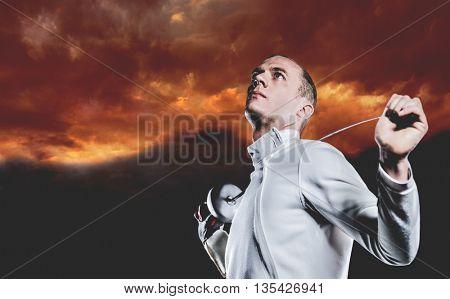 Swordsman holding fencing sword against gloomy sky