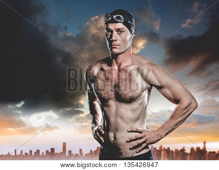 Swimmer standing with hand on hip against city on the horizon