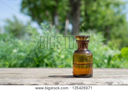 Little brown bottle with water or liquid on wooden board, against the background of vegetation.