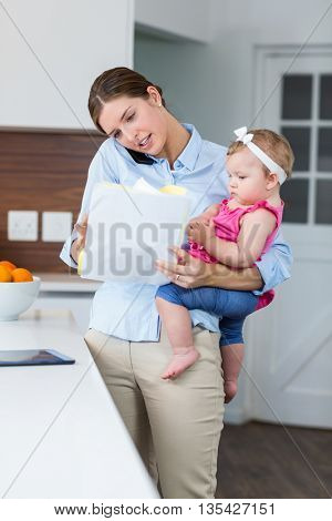 Woman looking in documents while carrying baby girl by table at home