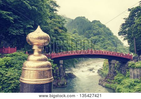 sacred wooden Shinkyo red bridge in Nikko Japan with focus on front pillar
