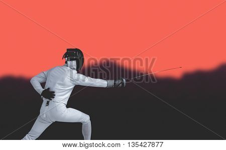Man wearing fencing suit practicing with sword against blurred mountains