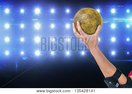 Female athlete with elbow pad holding handball against composite image of blue spotlight
