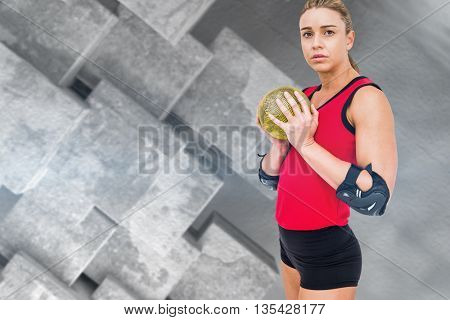 Female athlete with elbow pad holding handball against grey tile design