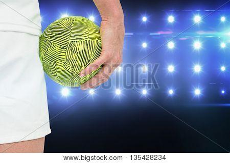 Sportswoman holding a ball against composite image of blue spotlight