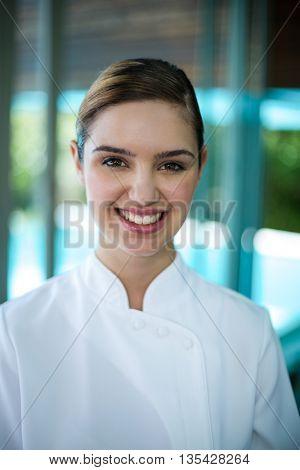 Portrait of confident female masseur standing in spa