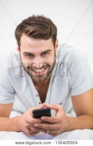 Close-up portrait of happy man using mobile phone while lying on bed at home