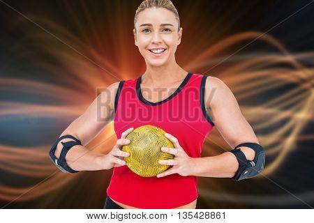 Female athlete with elbow pad holding handball against composite image of orange spotlight