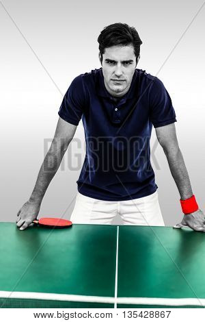 Confident male athlete leaning on hard table against grey background