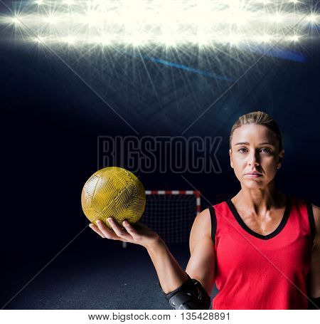 Female athlete with elbow pad holding handball against view of spotlights