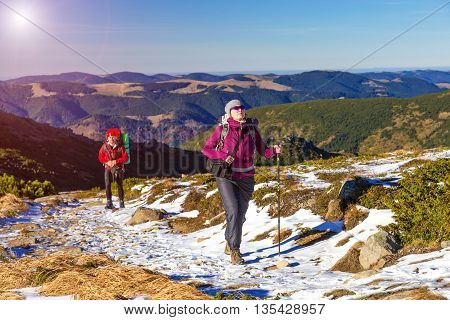 Male and Female Trekkers Walking Up on Snow Mountain Trail Carrying Backpacks and Using Hiking Poles Sun Shining on Clear Blue Sky