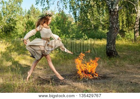 Beautiful woman with wreath of flowers jump through bonfire. Ivan Kupala Holiday Celebration. Russia