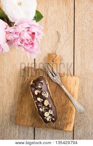 Eclair with chocolate ganache and nuts topping