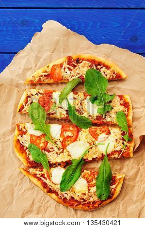 Rucola pizza on wrinkled craft paper with blue background vertical