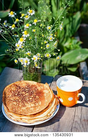 Bouquet of daisies, pancakes and glass of milk on a wooden table close-up view from above. Pancakes and milk for breakfast.