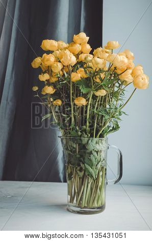 Fresh bunch of yellow summer flowers in glass vase on a white windowsill background. Cozy home rustic style decor, still life concept. Village life, home gardening. Tonal correction filter effect