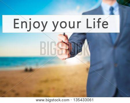 Enjoy Your Life - Businessman Hand Holding Sign