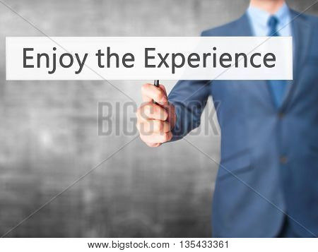Enjoy The Experience - Businessman Hand Holding Sign