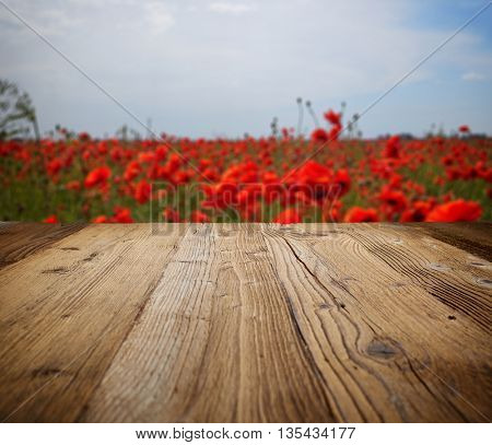 wooden rustic table in front of red poppies against sky with light burst.