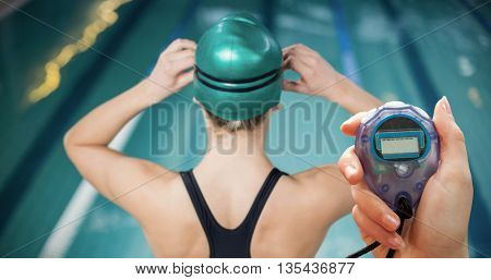 Close up of woman is holding a stopwatch against woman in swimsuit adjusting her goggles