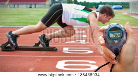 Composite image of a hand holding a timer against handsome sprinter on the starting line