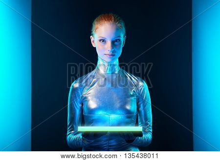 Futuristic cyber young woman in silver clothing holding lighting panel in her hands with copy space for your product. Sci-fi style.