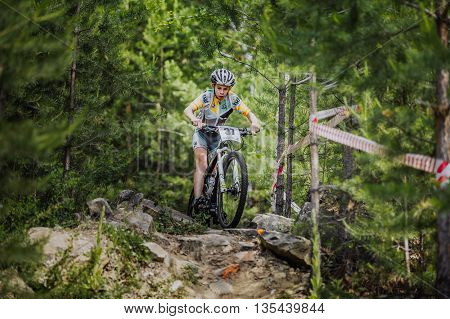 Kyshtym Russia - June 16 2016: young athlete rides a Bicycle on rocks in spruce forest during Championship of Russia on mountain bike