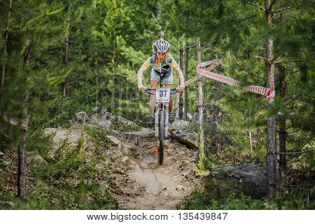 Kyshtym Russia - June 16 2016: young cyclist riding his bike on stones in spruce forest during Championship of Russia on mountain bike