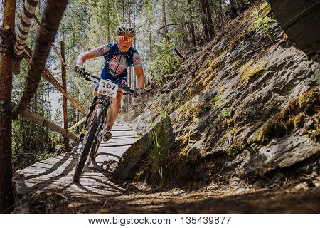 Kyshtym Russia - June 16 2016: man athlete cyclist rides down mountain a wooden bridge during Championship of Russia on mountain bike