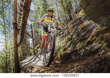 Kyshtym Russia - June 16 2016: closeup of woman athlete cyclist rides down mountain a wooden bridge during Championship of Russia on mountain bike