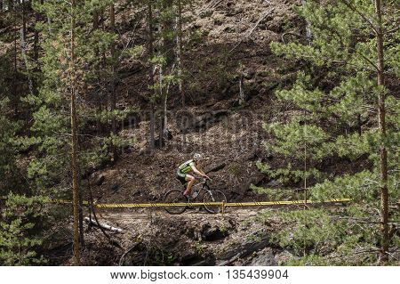 Kyshtym Russia - June 16 2016: General plan of a cyclist riding along mountains during Championship of Russia on mountain bike