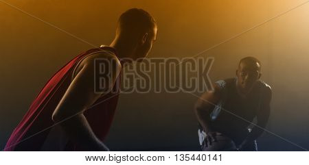 Two basketball player against a black background
