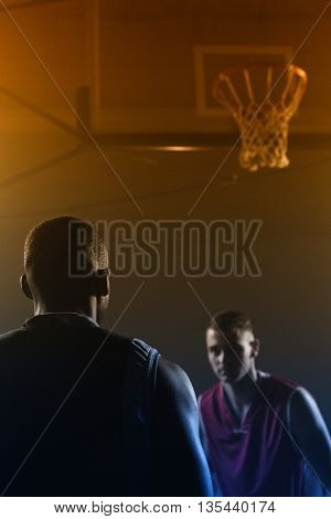 Concentrate basketball players playing in a gymnasium against a black background