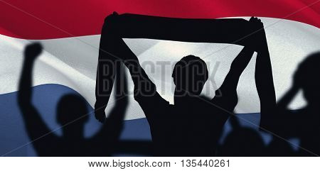 Silhouettes of football supporters against digitally generated dutch national flag