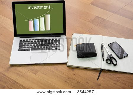 wooden desk with computer and notebook - chart Investment
