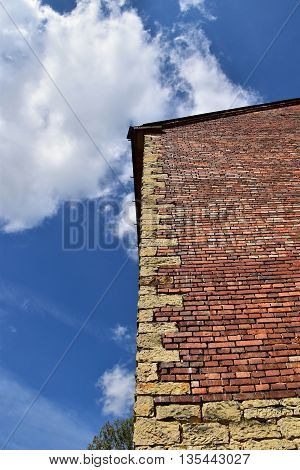 Corner stone, brick building, blue sky with clouds.