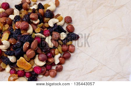 dried fruit lie on a light brown sheet of paper, all-sorts, nuts of different types, a fig, dry apricots, dates, prunes, a cranberry, raisin,