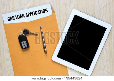 Top view of car loan application in envelope with car remote key pen and tablet.