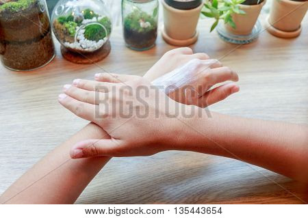 Young woman applying hands moisturizer lotion on wooden table.