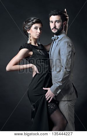Beautiful lady in dress with guy in suit. Young couple is hugging each other. Portrait of girl with attractive body and boy indoors in passionate pose. Beauty woman with lace gown